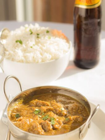 Ceamy coconut beef curry served in a balti dish with a bowl of rice and bottle of beer in the background.