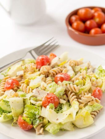 A plate of honey mustard turkey pasta salad with knife and fork on. A dish of cherry tomatoes and white jug in the background.