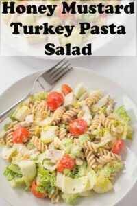 Honey mustard turkey pasta salad on a plate with a fork. Pin title text overlay at top.