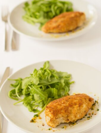 Two plates of baked chicken kievs served with lettuce on one in front of the other with knifes and forks beside.