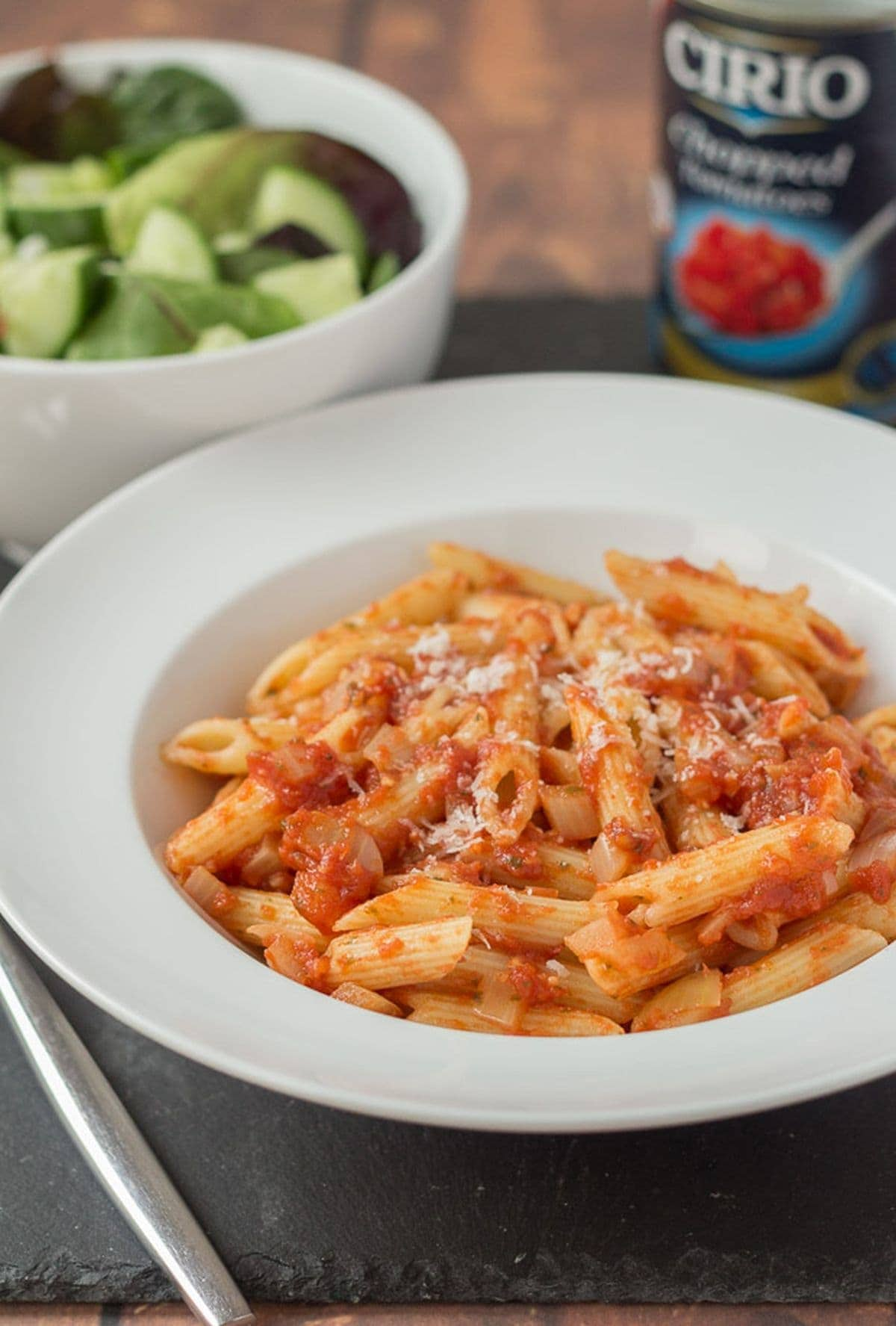 A plate of easy pasta arrabiata. Tin of tomatoes and a green salad in the background.