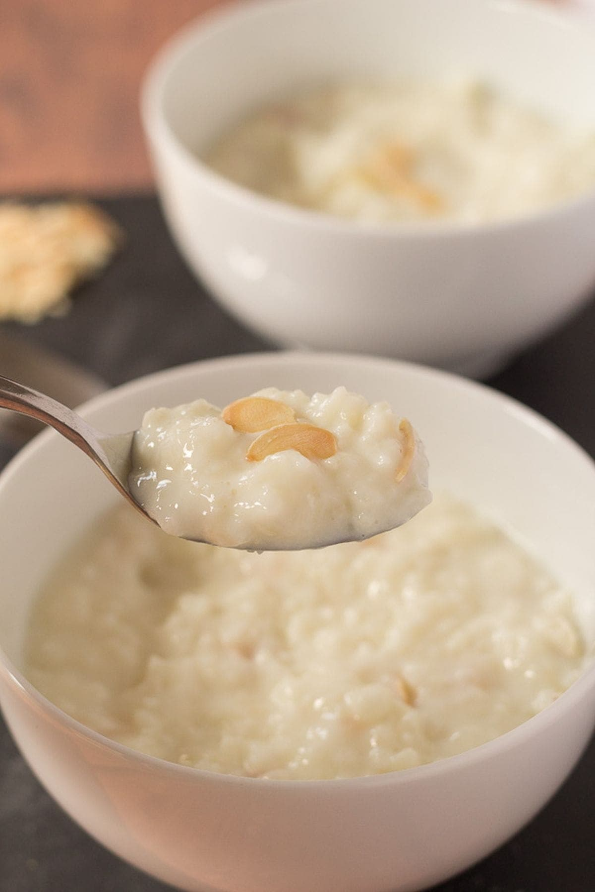Two bowls of easy rice pudding one in front of the other. A spoon lifting out a portion of the front bowl.
