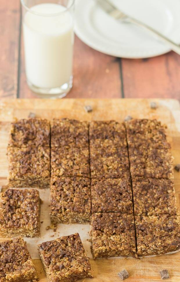 No bake chocolate oatmeal bars cut into 16 squares on a chopping board. Glass of milk and plate at the top.