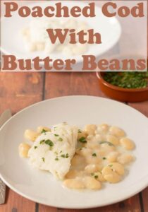 Two plates with poached cod with butter beans served on.