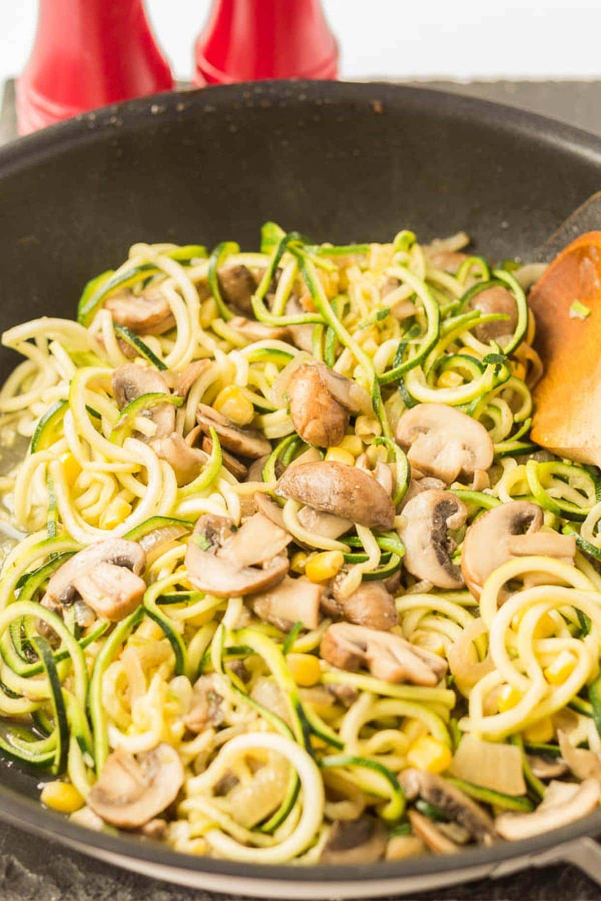 A pan of cooked zucchini mushroom pasta with a spatula to the side. Salt and pepper cellars in the background.