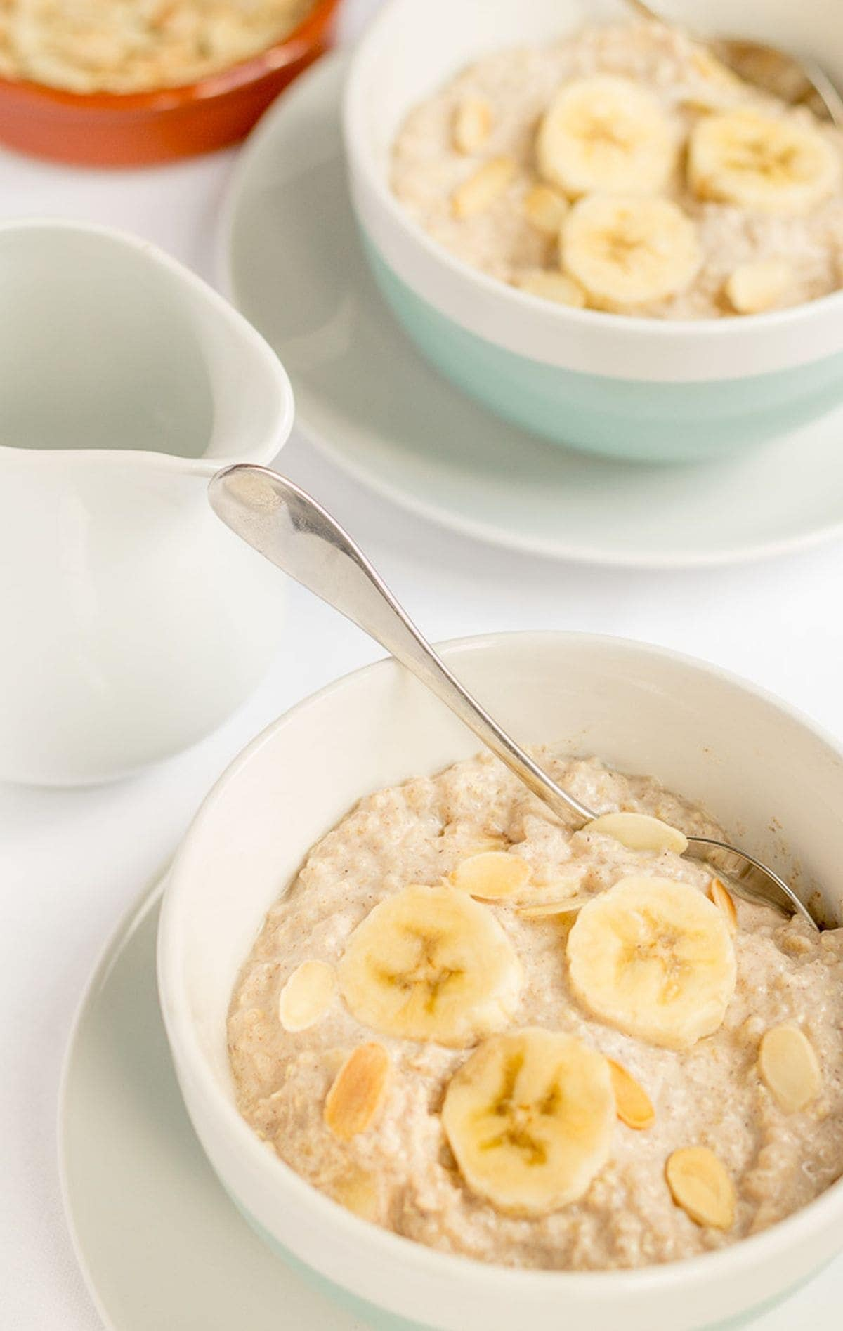 Two bowls of banana almond overnight quinoa. Front bowl with a spoon in it. Milk jug to the side. Other bowl to the back.