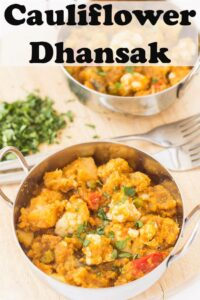 Two balti dishes of cauliflower dhansak one in front of the other with forks to each and coriander to garnish with.