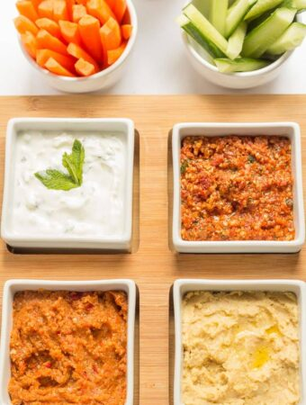 Birds eye view of four dishes containing low fat healthy dips.