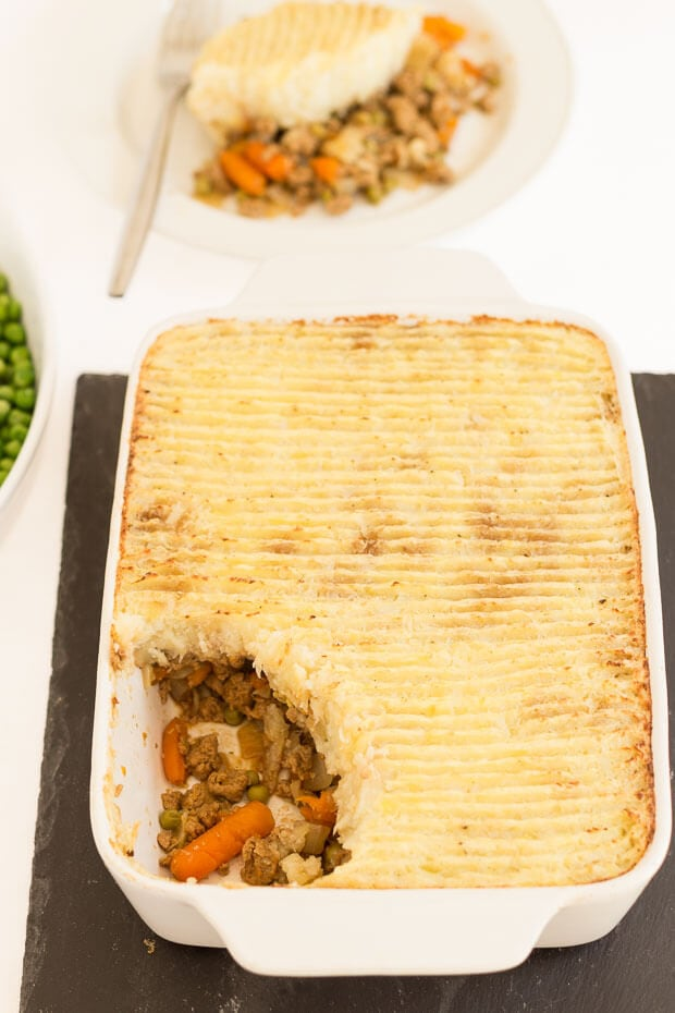 Birds eye view of a cooked vegetarian Quorn cottage pie with a portion removed to a plate at the top.