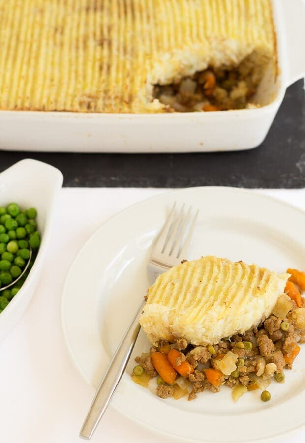 A portion of Quorn cottage pie served on a plate with a fork. Side dish of peas to the side and rest of the cottage pie at top.