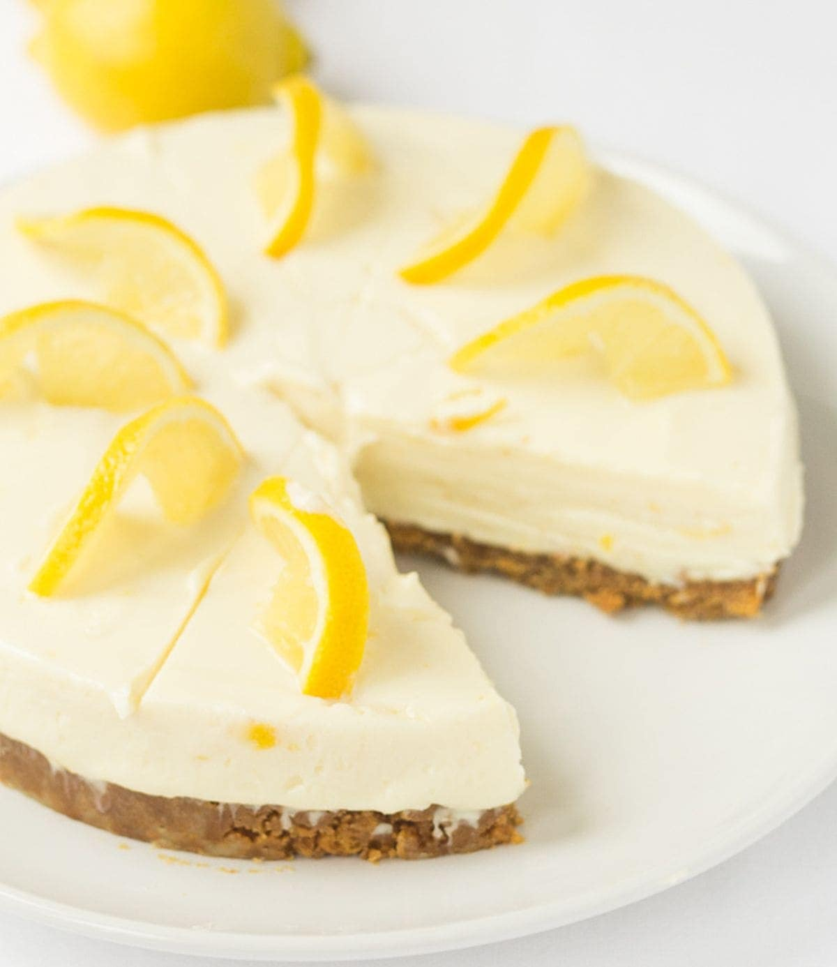 Lemon crunch cheesecake on a white plate with a slice removed.