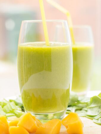 Two glasses of orange mango green smoothies with straws in. Sliced oranges at front of glasses.
