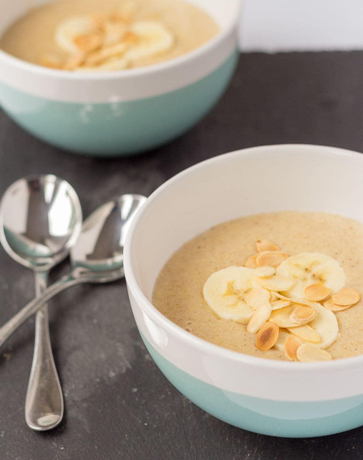 Two bowls of banana millet porridge decorated with sliced bananas diagonally across from each other. Serving spoons to the left.
