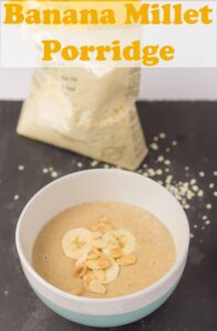 A bowl of banana millet porridge on a black slate with a bag of millet flakes in the background. Pin title text overlay at top.