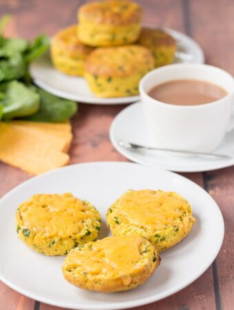 A plate of sweet potato spinach scones cut in half with melted cheese on. A cup of tea and the rest of the whole spinach scones on another plate in the background.