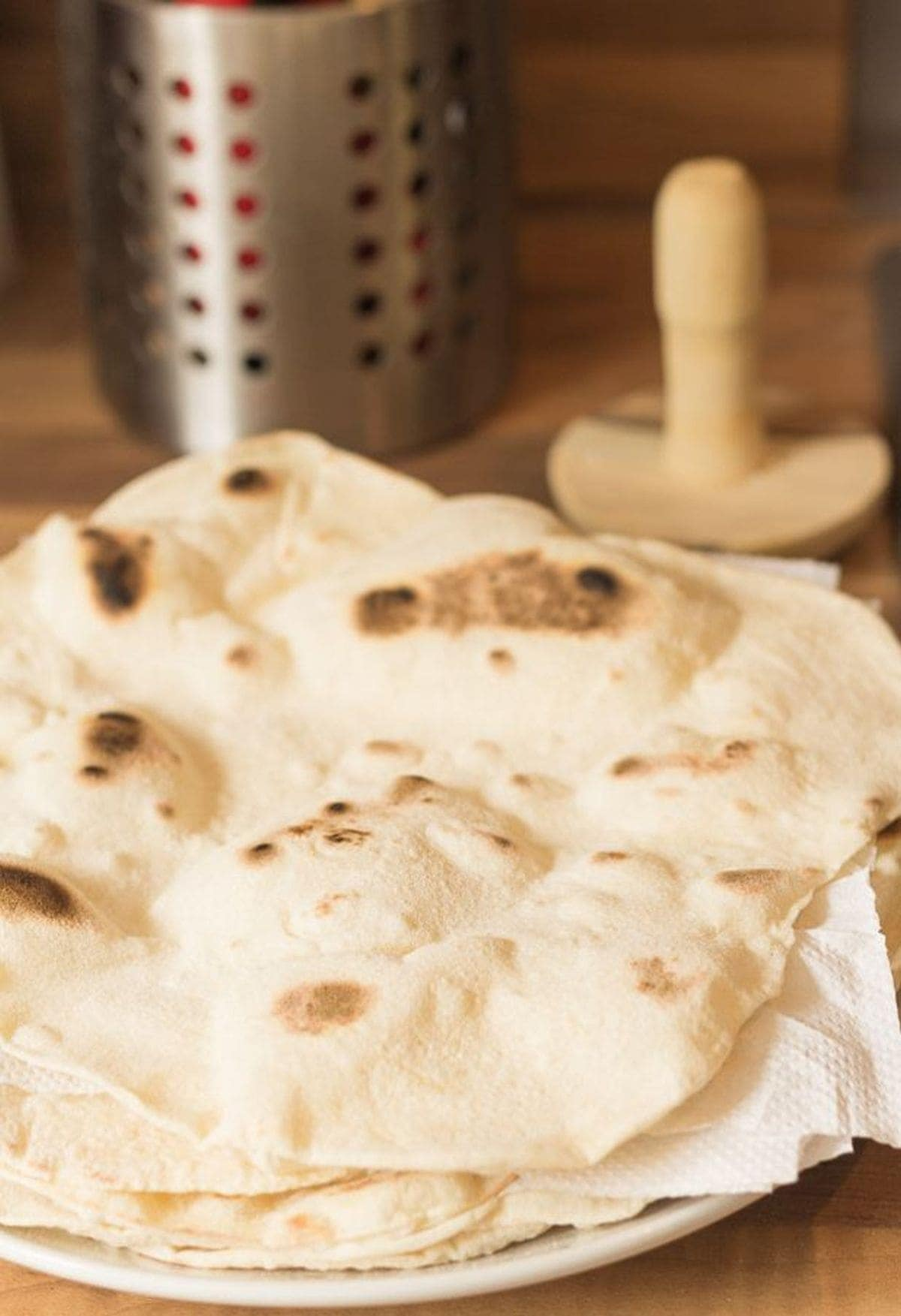 A plate of homemade naan breads seperated by kitchen roll.