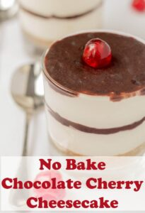 No bake chocolate cherry cheesecake in a glass decorated with a cherry and a teaspoon beside ready to eat.
