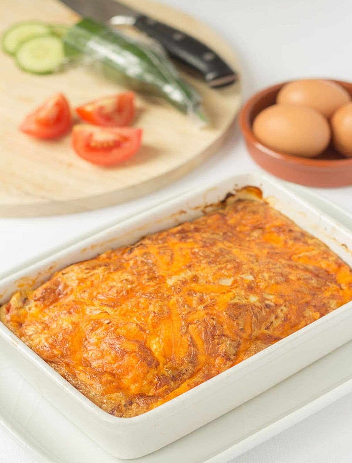 A casserole dish of cooked baked cheese and tomato omelette just removed from oven. Chopping board with salad on and dish of eggs in the background.