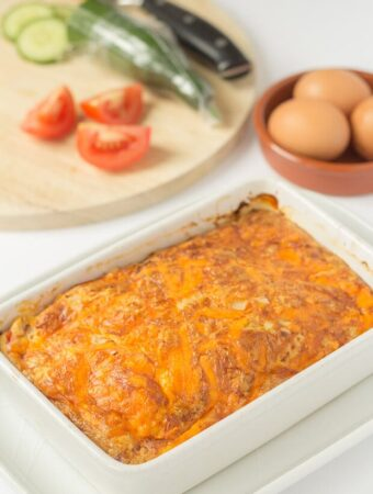 Oven baked cheese and tomato omelette in white backing dish sitting in front of a chopping board with tomatoes and cumumber on.