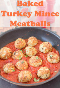 Baked turkey meatballs in tomato and chilli sauce simmering in a pan of tomato sauce.