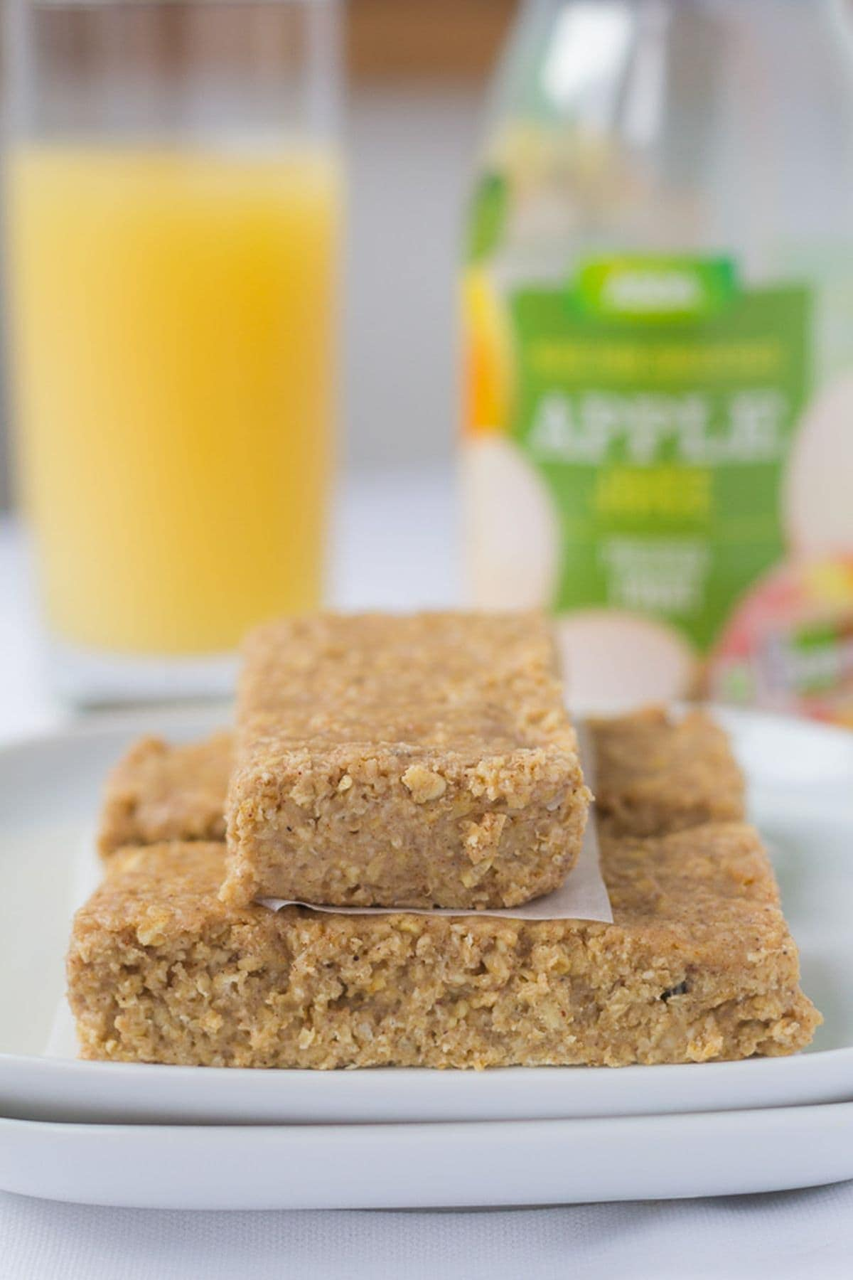 A plate of three no bake apple and cinnamon oat bars with a glass of apple juice and a plastic bottle juice bottle in the background.