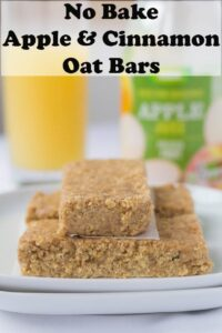 No bake apple and cinnamon oat bars stacked on a plate with a glass of apple juice behind.