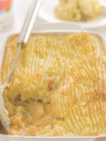A casserole dish of turkey and courgette bake with a portion taken out and a serving spon on top.