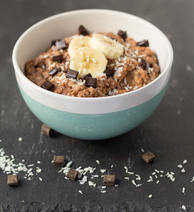 Close up of a bowl of chocolate chip banana coconut porridge on a black slate with chunks of chocolate and grated coconut decorated around.