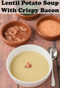 A bowl of lentil and potato soup topped with crispy bacon. Dishes of chopped bacon and lentils in the background. Soup spoon to the side. Pin title text overlay at top.