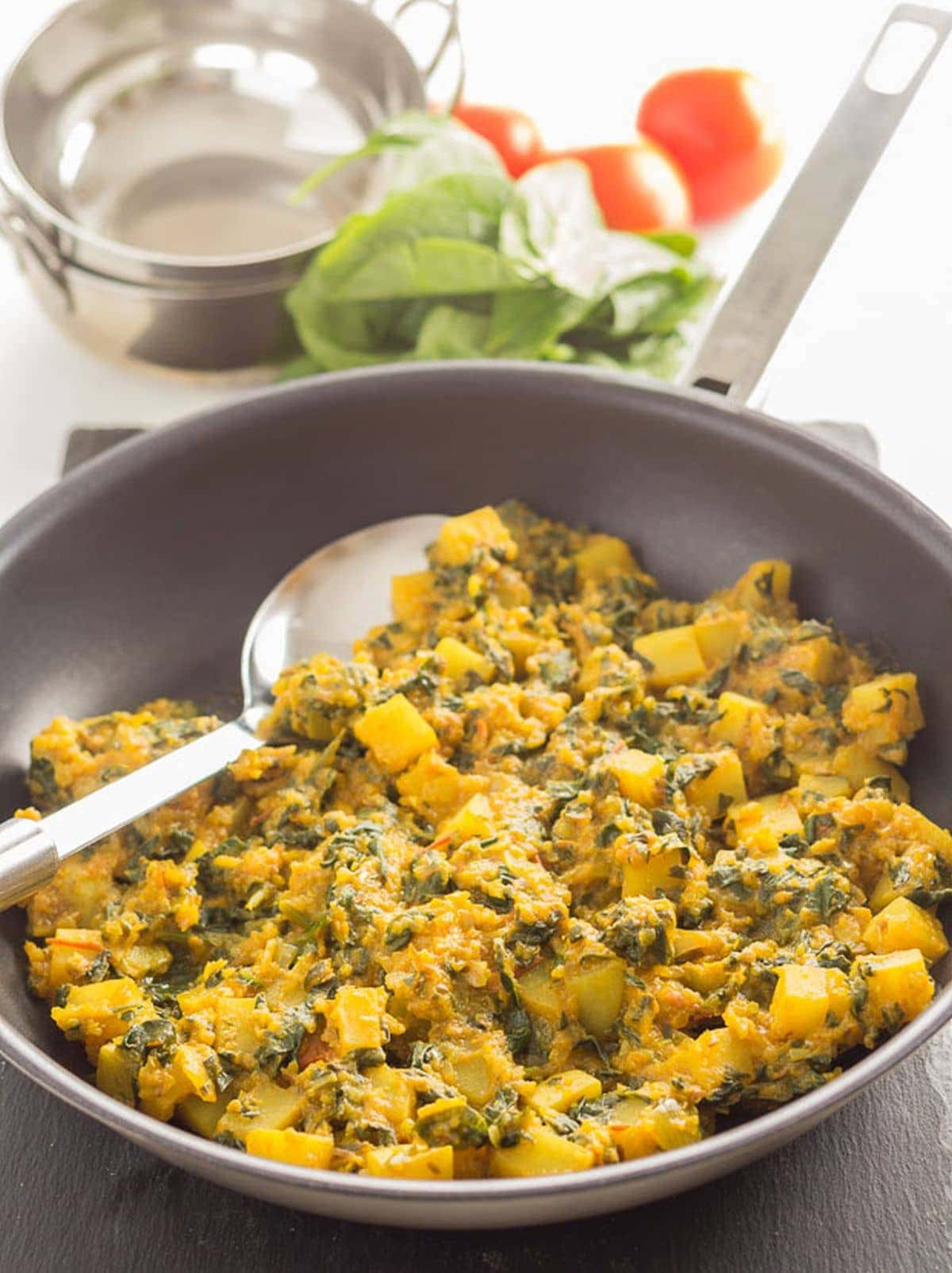 A pan of potato and spinach curry with a serving spoon in. Balti dishes and spinach leaves as decorations in the background.