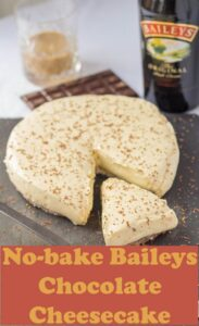 Baileys chocolate cheesecake on a grey slate with a slice taken out of it and a bottle of Baileys in the background.