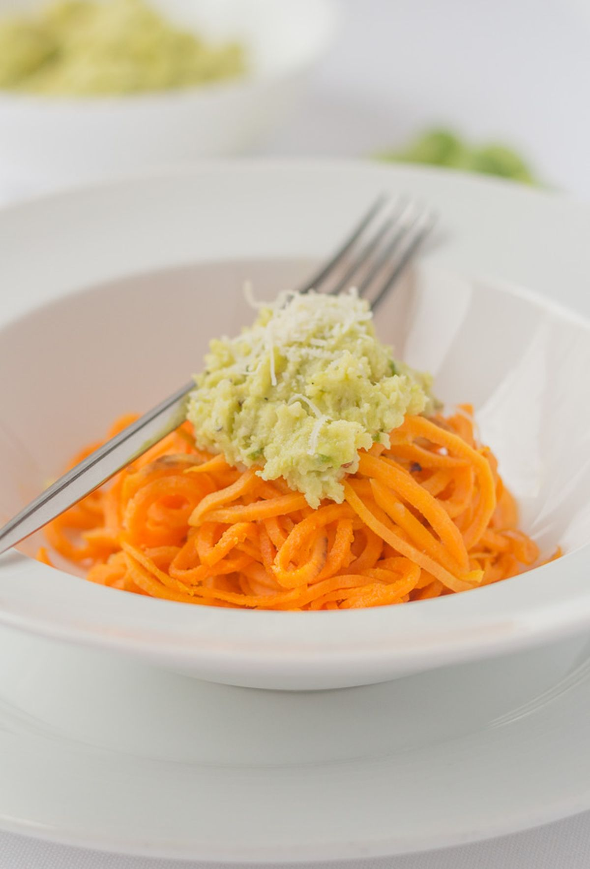 A bowl of spiralized sweet potato topped with brussels sprout pesto and a fork to the side.