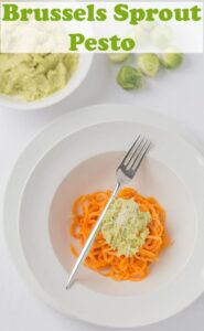 Brussels sprout pesto on spiralized baked sweet potato in a bowl.