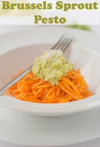 Brussels sprout pesto topped on spiralized sweet potatoes. Pin title text overlay at top.