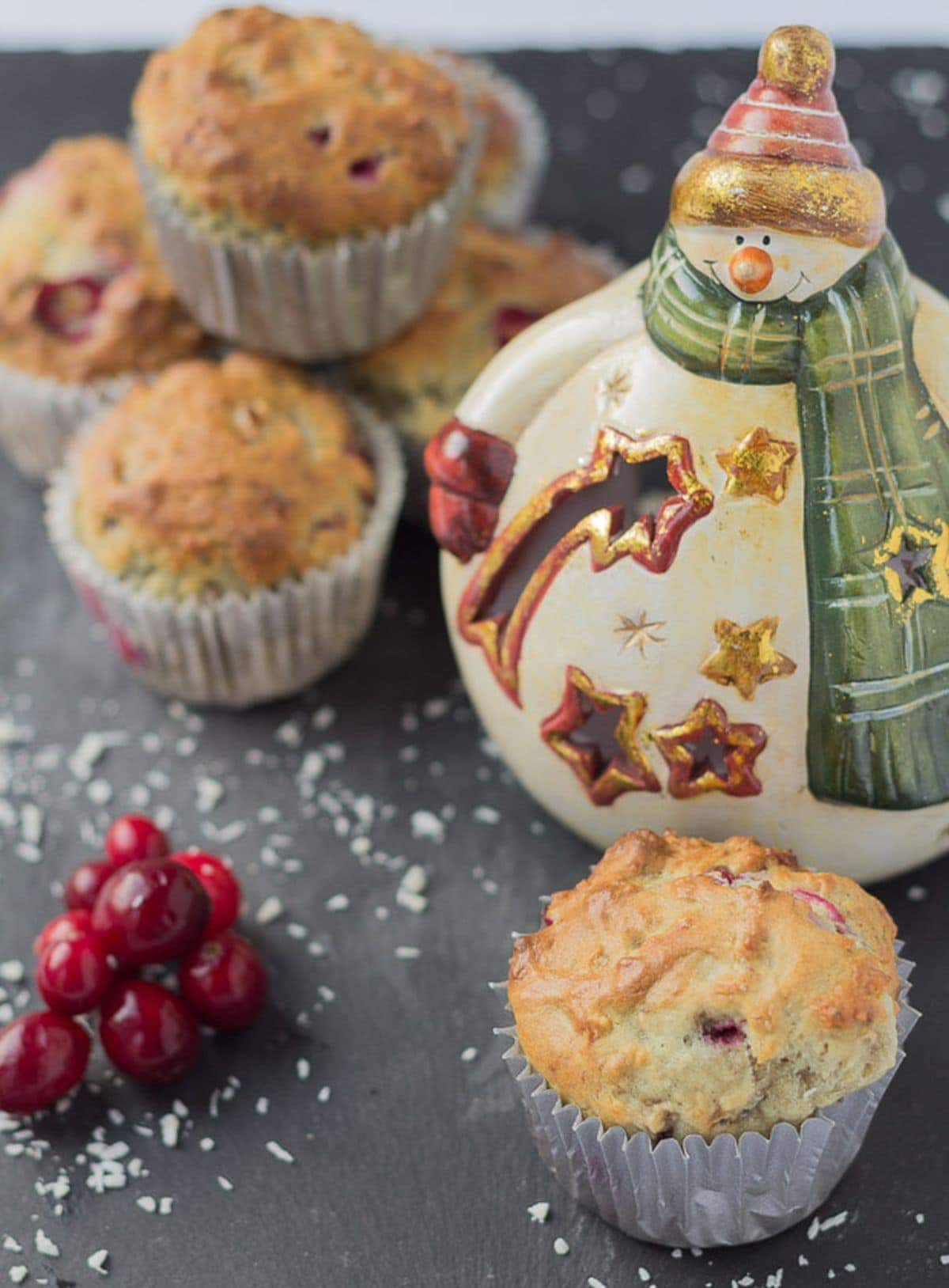 Cranberry banana muffins on a slate. One at the front a pile of cranberries to the side and a porcelian snowman with a stack of the muffins in the background.