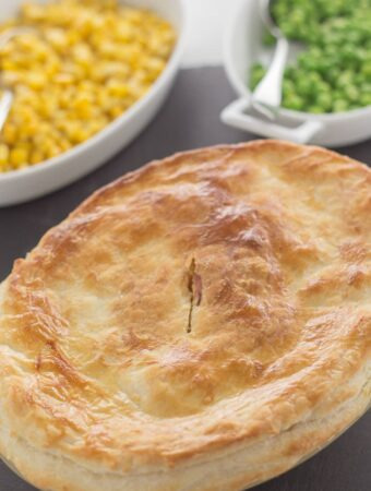 Turkey and leek pie at the bottom with side dishes of sweetcorn and peas at the top.