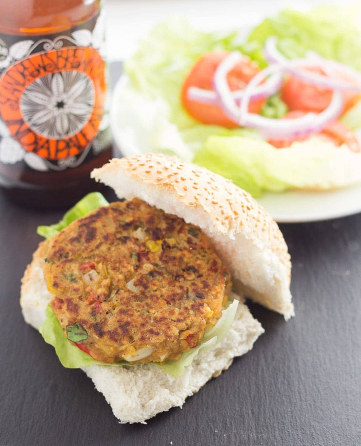 A spicy lentil burger on a burger bun. Plate of toppings and a bottle of beer in the background.