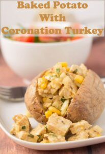 Baked potato with Coronation turkey in front of a bowl of salad.