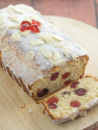 Cherry bakewell loaf cake on a chopping board with a slice taken off the front.