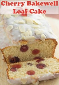 Cherry bakewell loaf cake on a bread board facing forward with a slice cut off and lying in front of the cake so delicious inside filled with cherries can be seen!