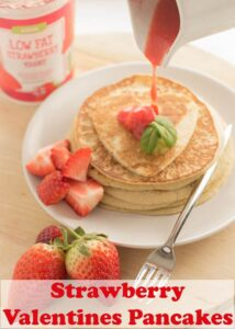 A stack of strawberry valentines pancakes decorated with strawberries and strawberry sauce being poured over the top.