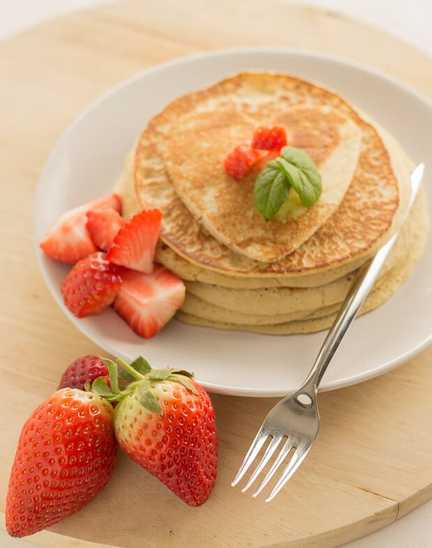 A stack of strawberry valentines pancakes on a plate with some chopped strawberries to the side. A fork and whole strawberries in front.