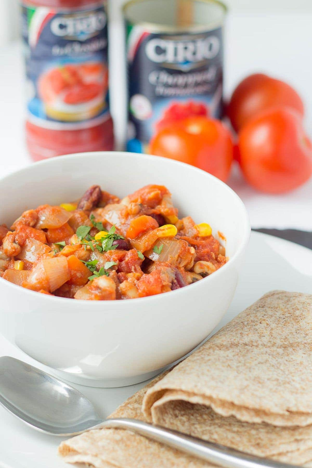 A bowl of easy vegan chilli with a spoon in front and wholemeal wraps to the side. Cans of chopped tomatoes and three tomatoes in the background.
