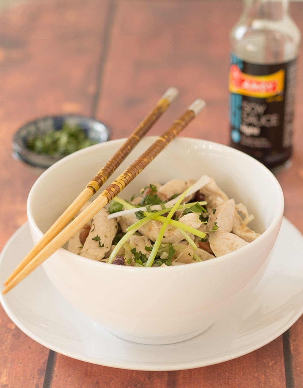 A bowl of chicken and mixed bean stir fry with chopsticks sitting on top. Soy sauce and a dish of chopped coriander in the background.