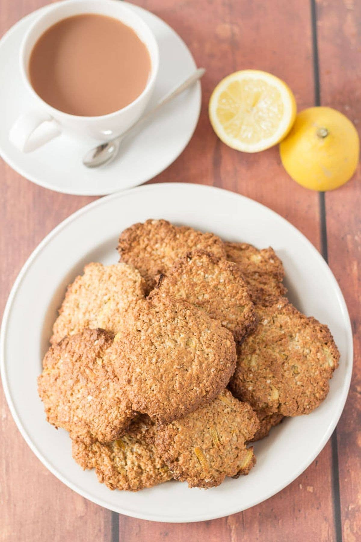A plate of lemon oat cookies with a cup of tea and a lemon cut in half at the top of the picture.