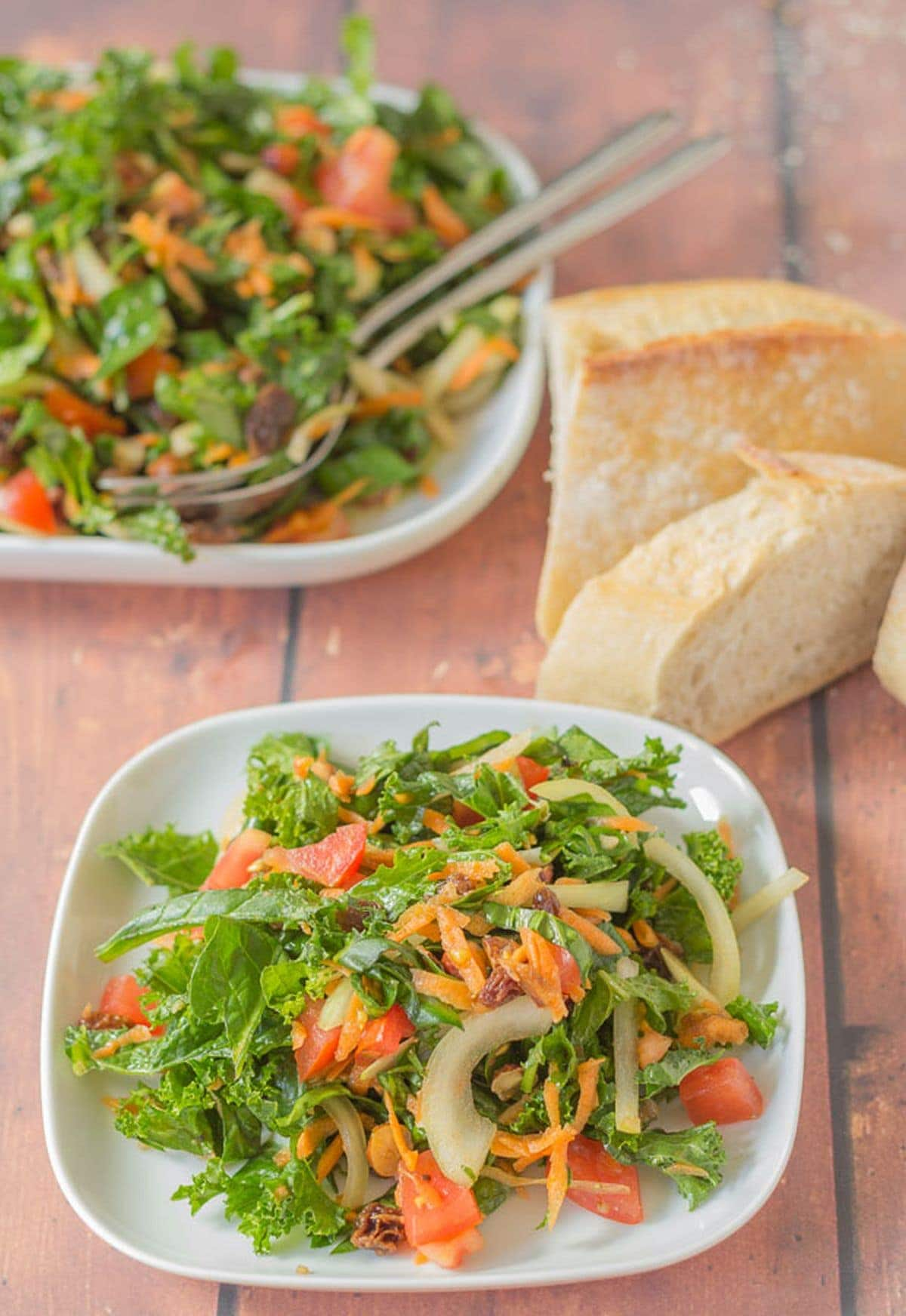 Two square plates of shredded kale and spinach salad one in front of the other with some sliced bread in between.