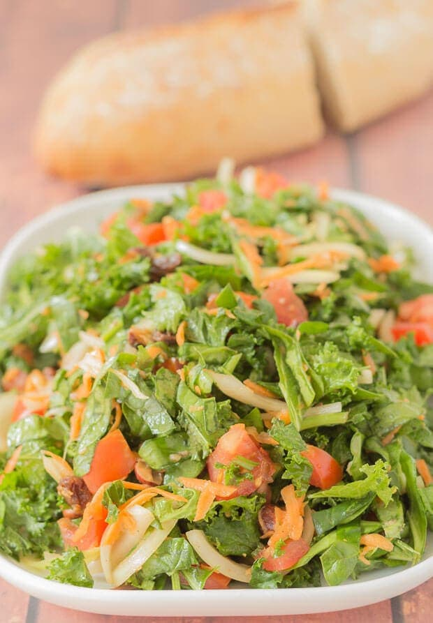 Close up of Shredded kale and spinach salad on a serving plate. A loaf of bread cut in half in the background.