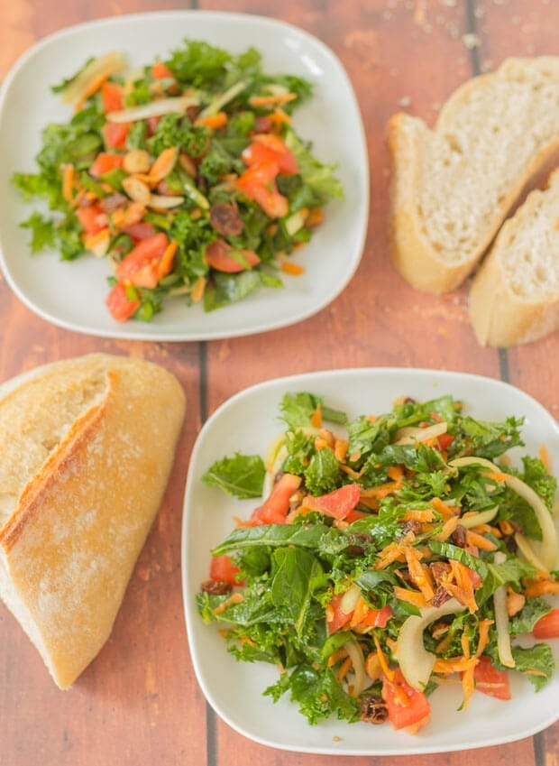 Two plates of shredded kale and spinach salad with a loaf of bread and slices of bread decorated around.