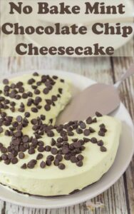 Mint chocolate chip cheesecake with a slice taken out of it and a serving slicer in its place.