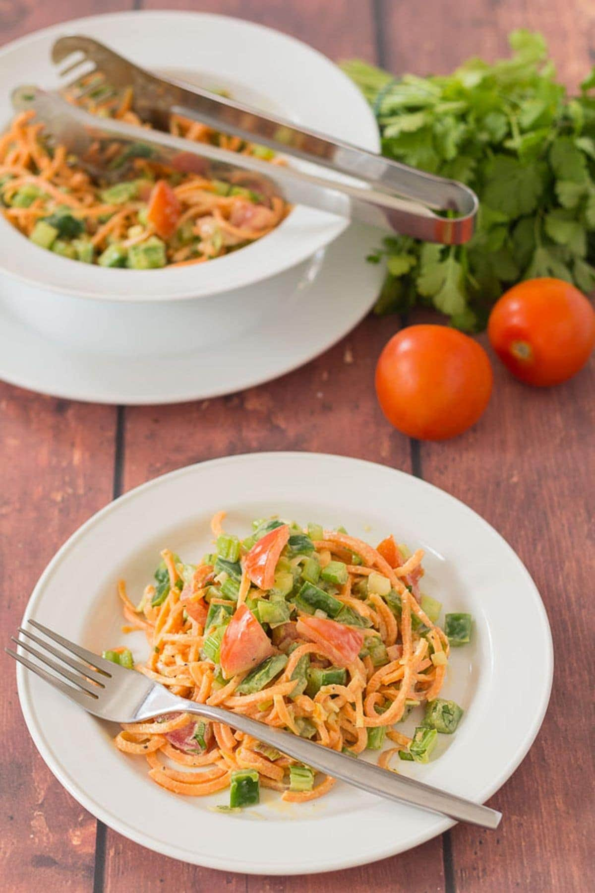 A plate of spiralized sweet potato salad with the serving bowl in the background. Tomatoes and lettuce in between as decoration.